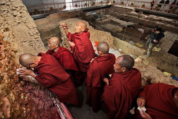 Monaci in pellegrinaggio al tempio di Lumbini. Sullo sfondo gli scavi archeologici che interessano l'area (Ira Block, National Geographic)