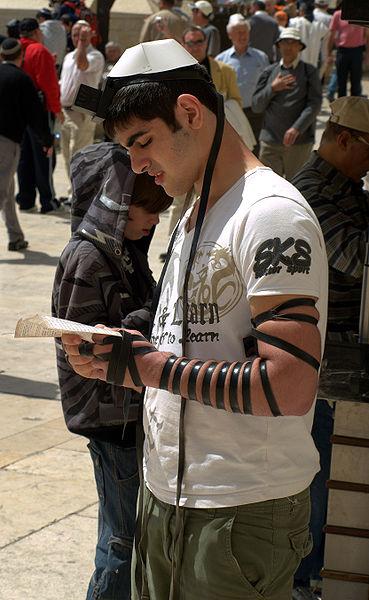 Un uomo davanti al Muro Occidentale che indossa i tefillin della testa e del braccio (wikimedia)