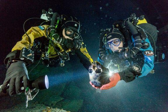 Due sub impegnati nella spedizione archeologica nell'Hoyo Negro trasportano delicatamente il teschio di Naia su un tavolo rotante subacqueo, dove sarà fotografato per crearne una copia 3D (National Geographic)