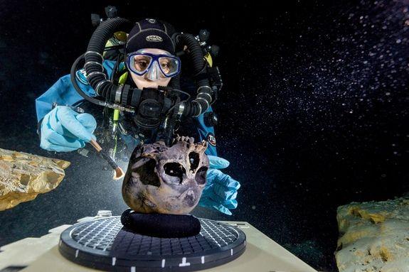 Susan Bird, archeologa e sub professionista, spazzola il teschio di Naia sul ripiano rotante in fondo alla grotta, mentre un collega lo fotografa (National Geographic)