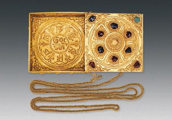 Un contenitori di profumi con catenella d'oro. È decorata con petali di loto e sette caratteri in sanscrito. Le gemme includono quattro zaffiri, cinque rubini e un turchese. (Courtesy of Chinese Cultural Relics)