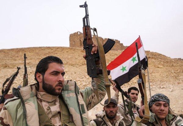 I soldati governativi con una bandiera siriana vicino al castello medievale di Palmira (Valery Sharifulin/TASS via Getty Images)