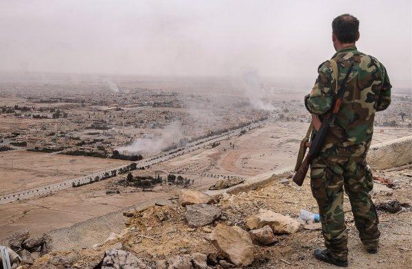Un soldato dell'esercito siriano guarda Palmira dall'alto del castello medievale della città (Valery Sharifulin/TASS via Getty Images)