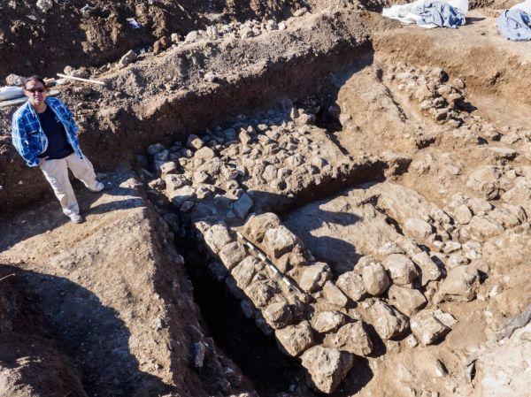 L'archeologo Ronit Lupo di fianco ai resti di una delle antiche abitazioni scoperte nel quartiere di Shuafat (Assaf Peretz/Israel Antiquities Authority)