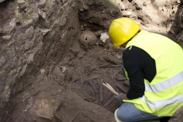 Un archeologo controlla i resti umani rinvenuti (ANSA/AP Photo/Alessandra Tarantino)
