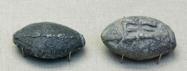 """Proiettili di piombo ovali. Su un lato è incisa una saetta, mentre sull'altro l'equivalente della scritta """"Prendi Questo"""". Piombo del IV secolo a.C. proveniente da Atene (Wikimedia)"""